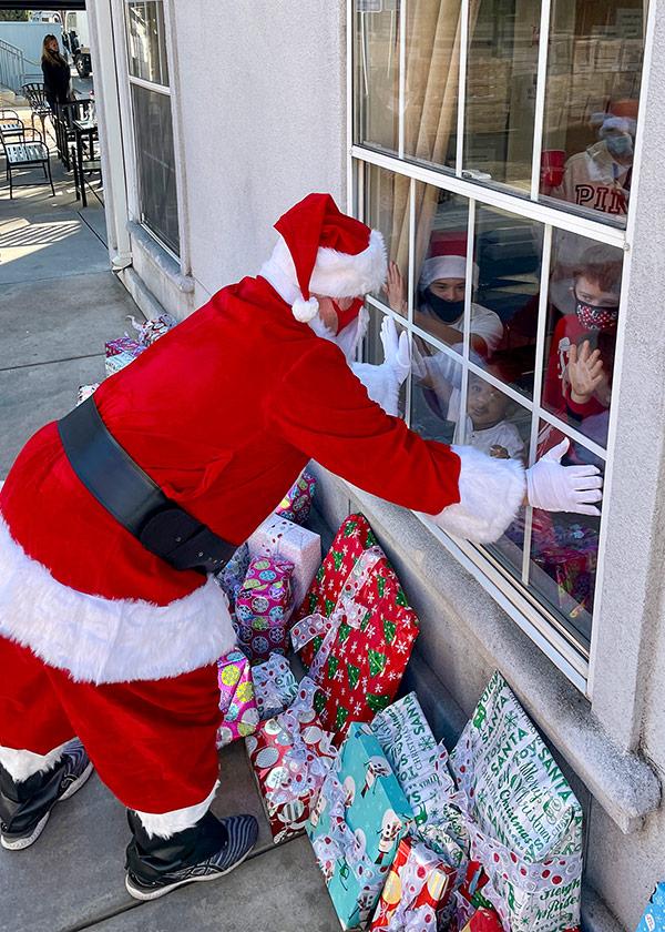 Journey Santa looking in window at kids